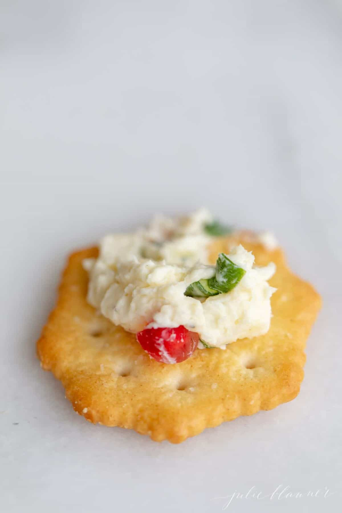 A white surface with a single cracker with a serving of holiday cheese ball on top.