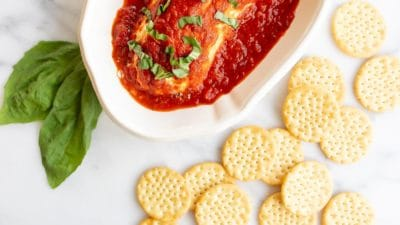 A white bowl filled with baked goat cheese covered in marinara, crackers scattered to the side.