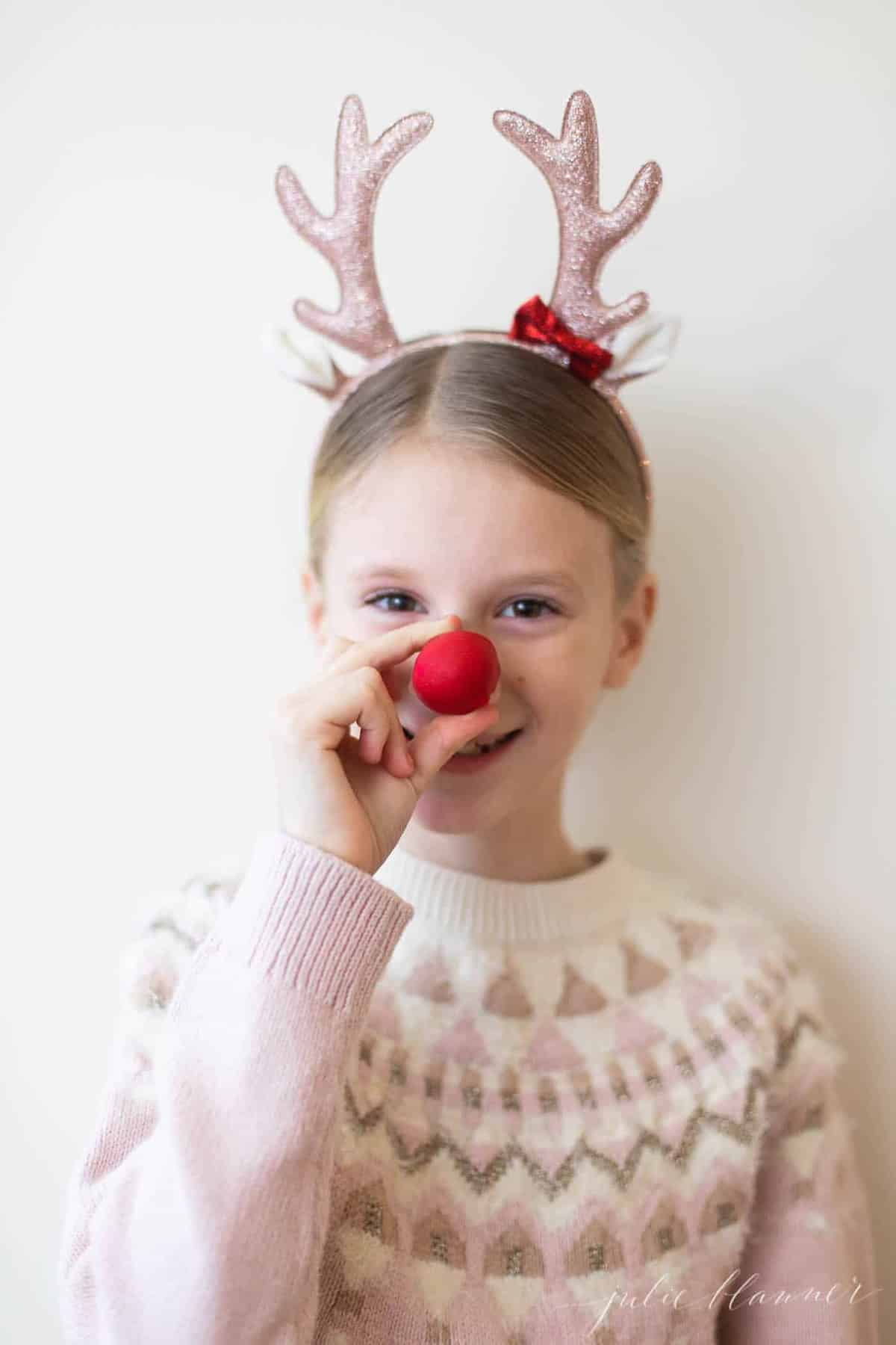 girl holding up a rudolph nose with antlers on