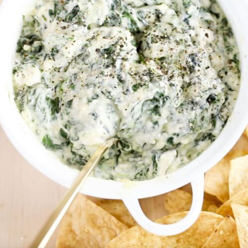 spinach dip in white dish with gold spoon
