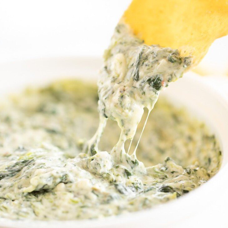 A tortilla chip into a white bowl full of cream cheese spinach dip.