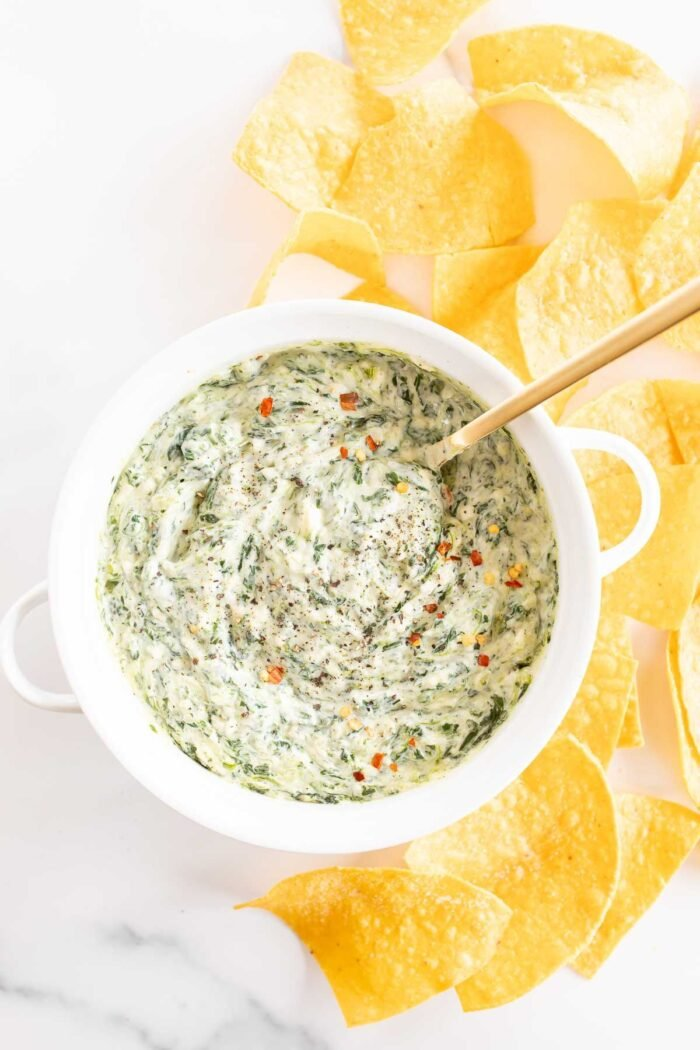 A white bowl full of spinach dip with cream cheese, gold spoon in the bowl and tortilla chips to the side.