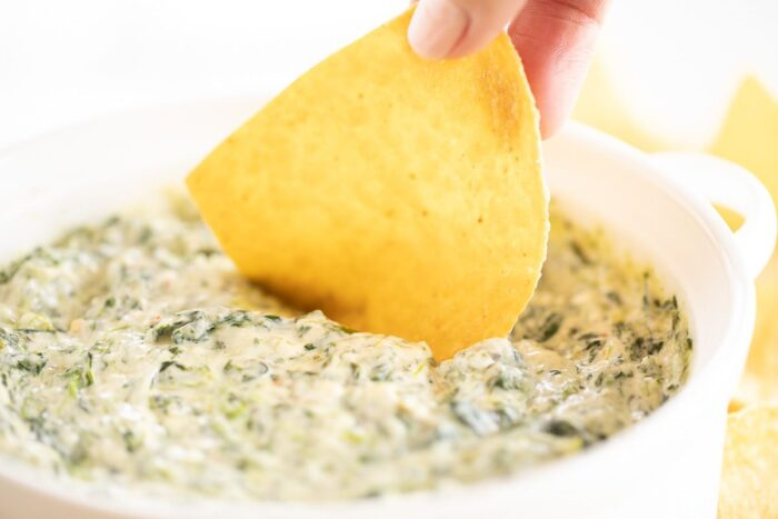 Fingers dipping a tortilla chip into a white bowl full of cream cheese spinach dip.