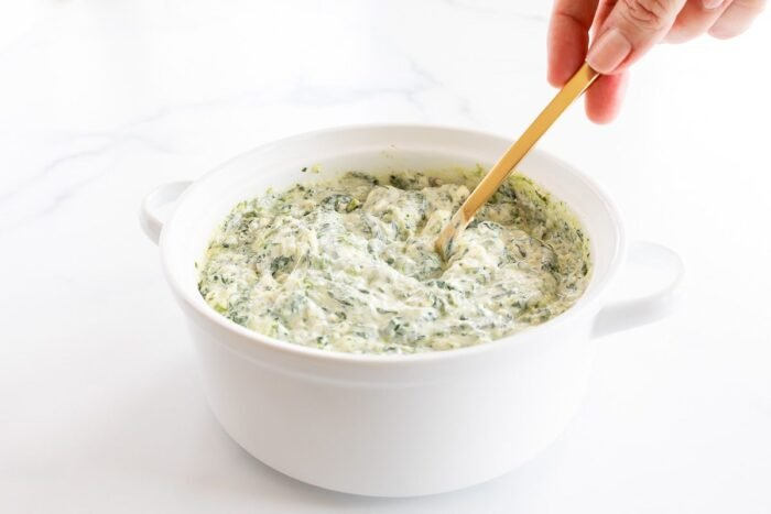 Cream cheese spinach dip being mixed in a white bowl.