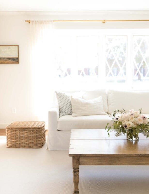 A white living room with storage containers integrated as part of the decor, like a lidded basket as a side table.