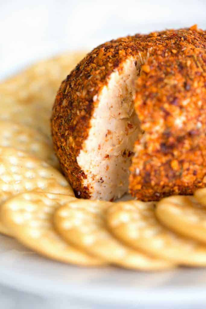 A cheeseball on a platter, slice cut out, crackers surrounding.