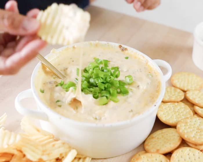 A hand pulling a chip full of a cheesy easy dip recipe in a white bowl.