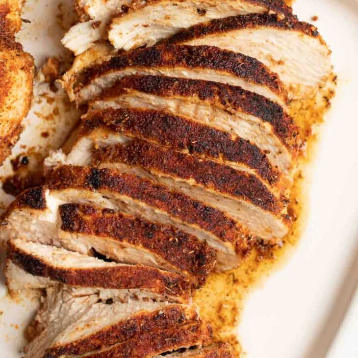A white platter with sliced blackened chicken breasts.