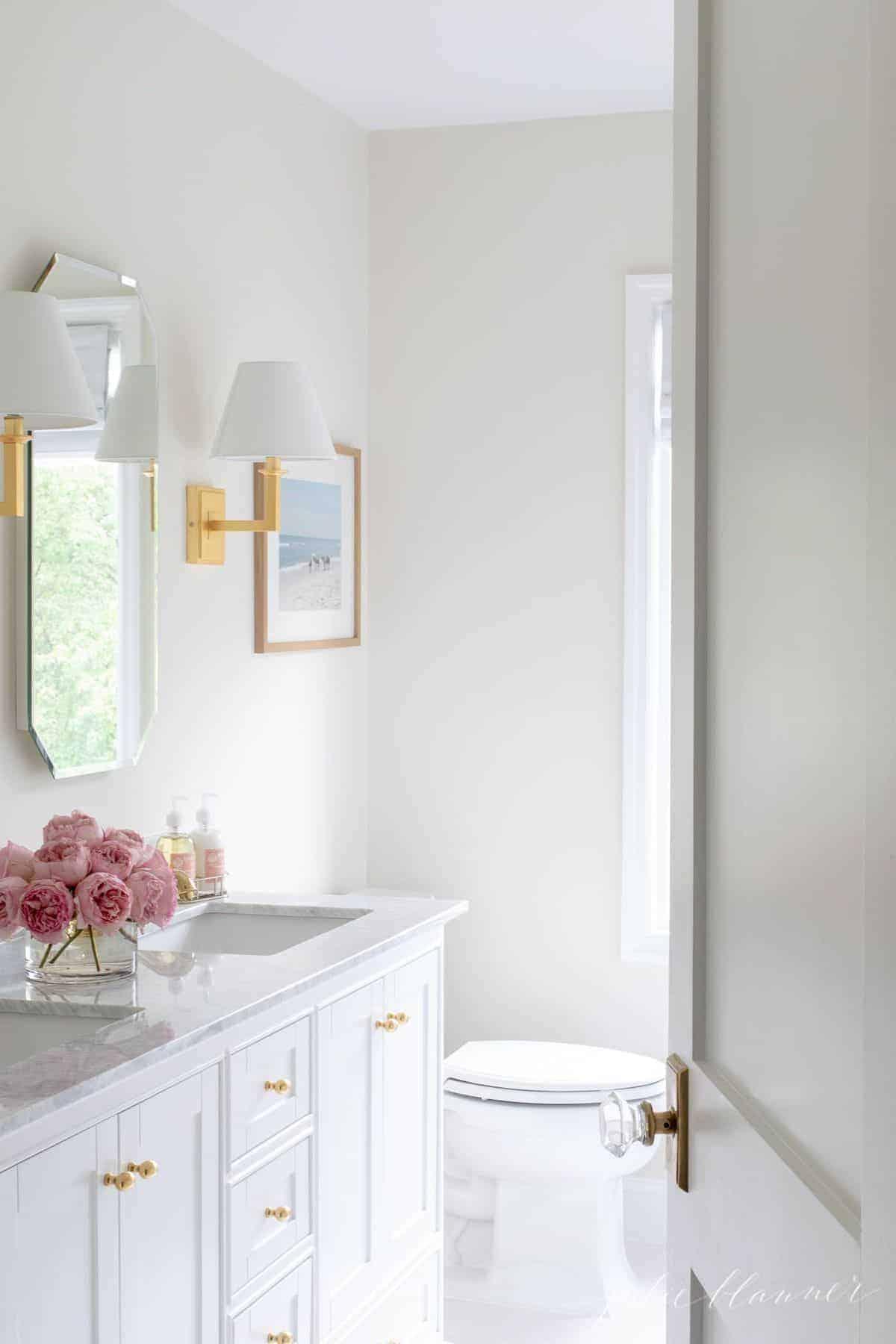 White bathroom with double vanity, white tile floor.