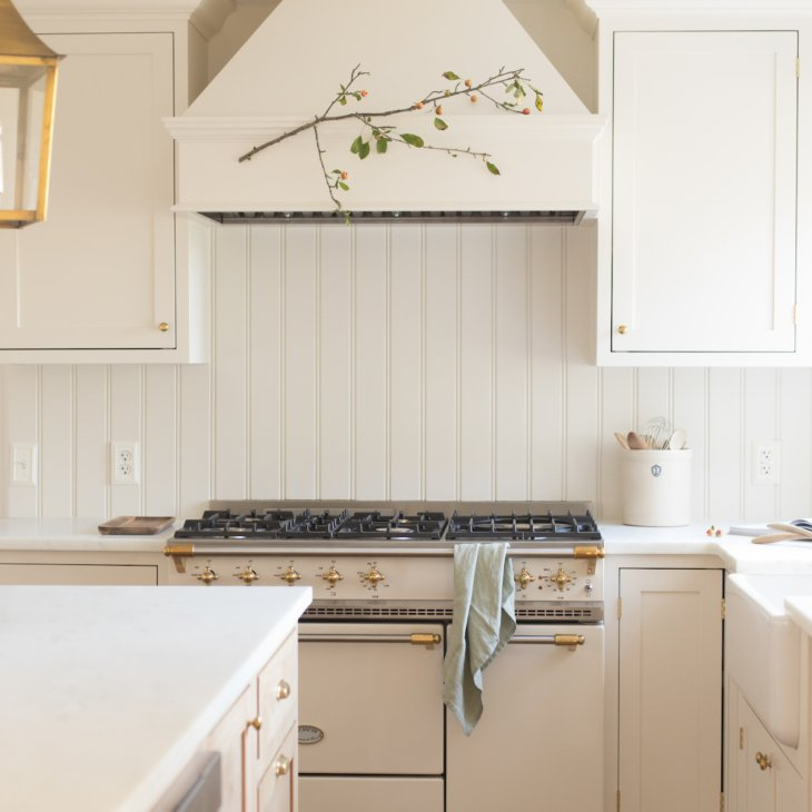 A soft wood toned kitchen island with a built in microwave drawer and brass lanterns above.
