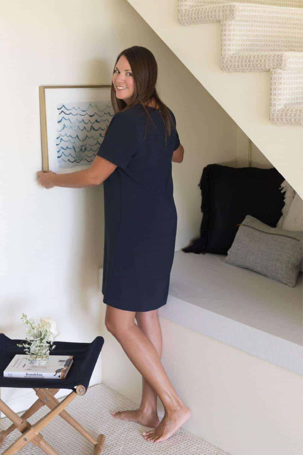 Woman in a blue dress hanging a piece of framed art in a cozy living room.