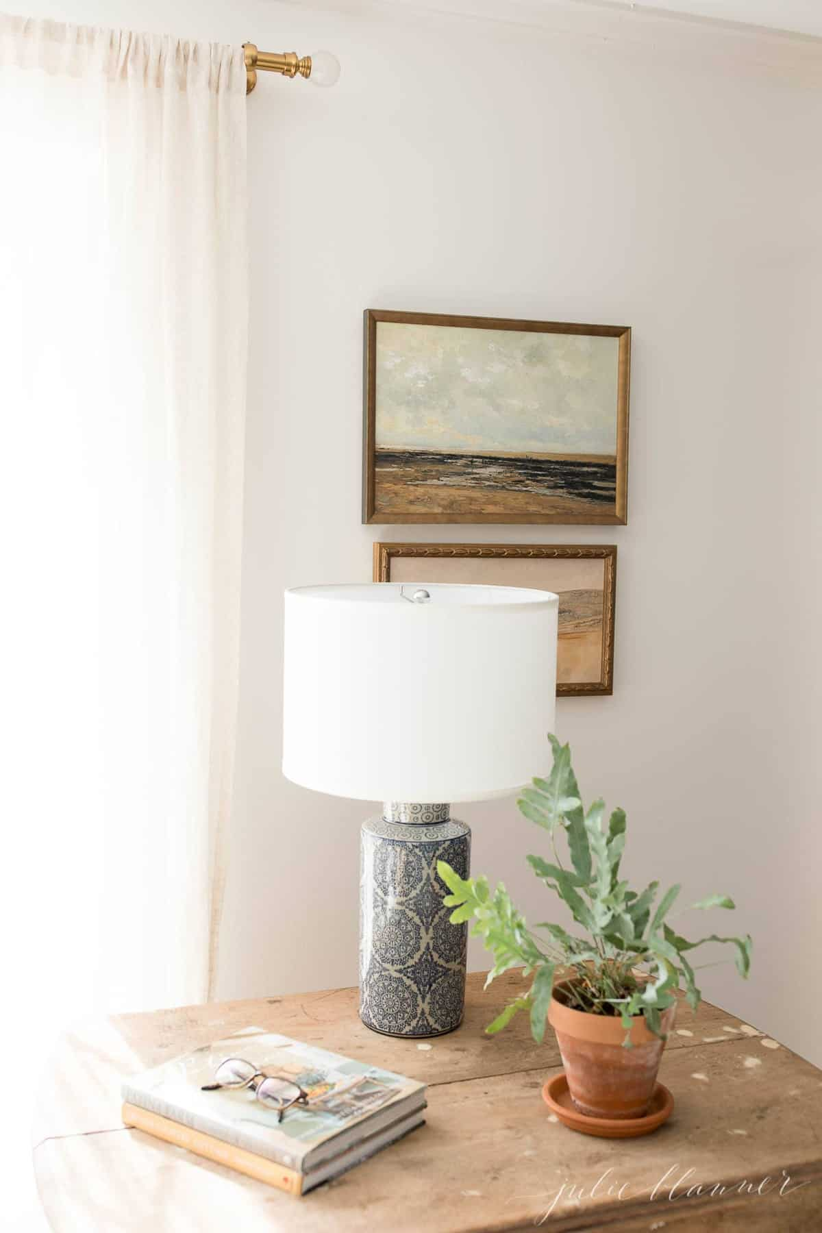A cozy living room with a wooden accent table, lamp plant and art in the background.