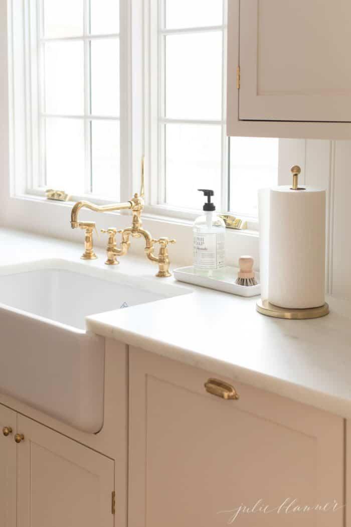 cream kitchen cabinets, farmhouse sink, brass faucet.