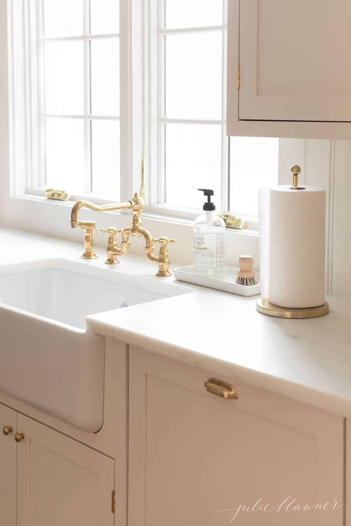 cream kitchen cabinets, farmhouse sink, brass faucet.