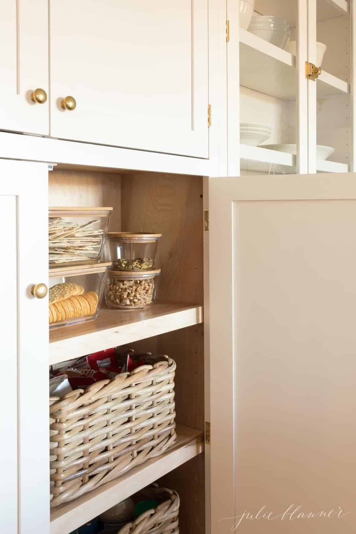 Looking into a pantry cabinet, clear jars and baskets storing food items.