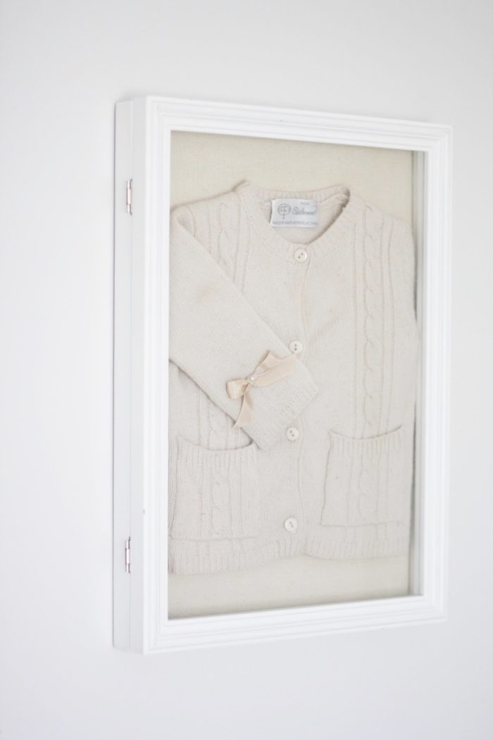 A white framed baby sweater used as diy wall art.