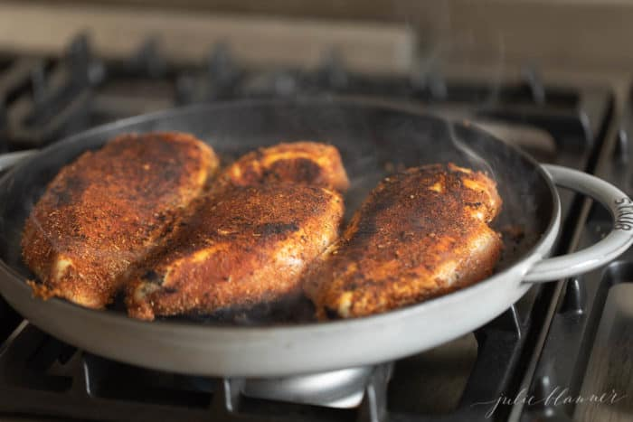 A cast iron pan on the stove top cooking seasoned chicken.