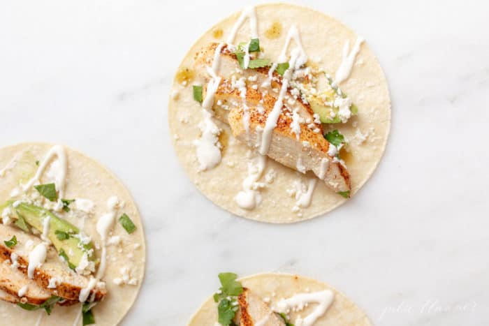 White surface with three corn tortillas filled with chicken taco ingredients.