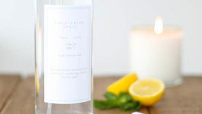 A clear glass spray bottle with a custom label, filled with natural all purpose organic cleaner - lemons and a candle in the background.