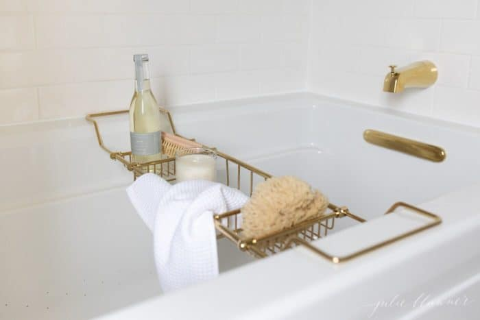 White bathtub with a brass tub tray filled with bath accessories.