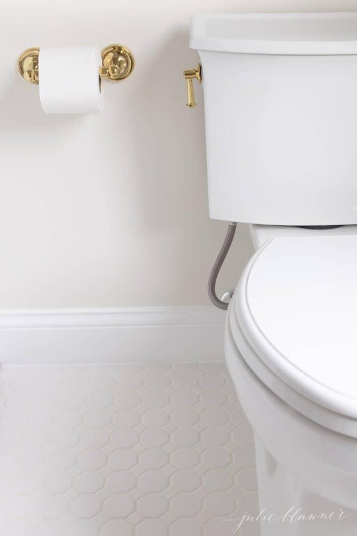 A white tile floor near a toilet in bathroom.