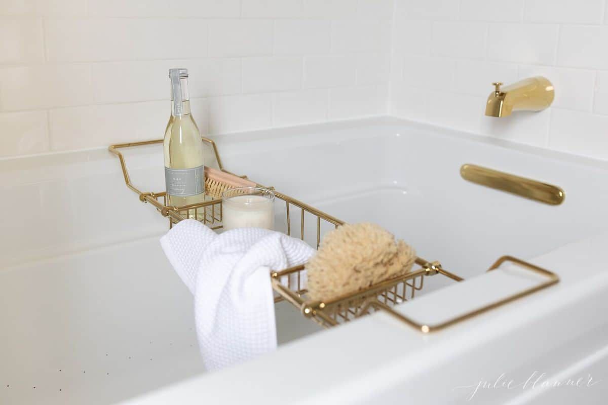 A brass bath tray with various items like a candle, champagne, sponge, and a wash cloth to make the ultimate bath experience.