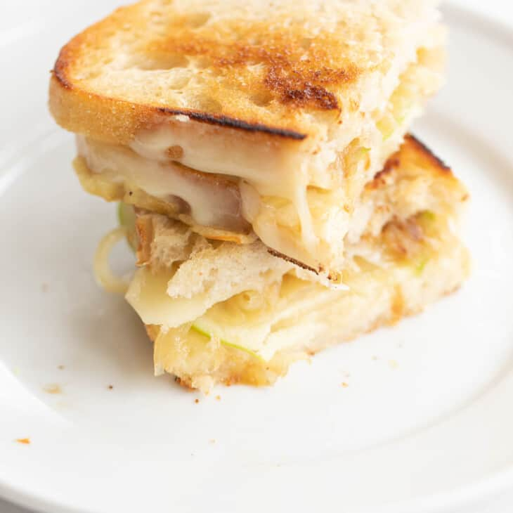 White plate with a sliced and stacked gourmet grilled cheese sandwich.
