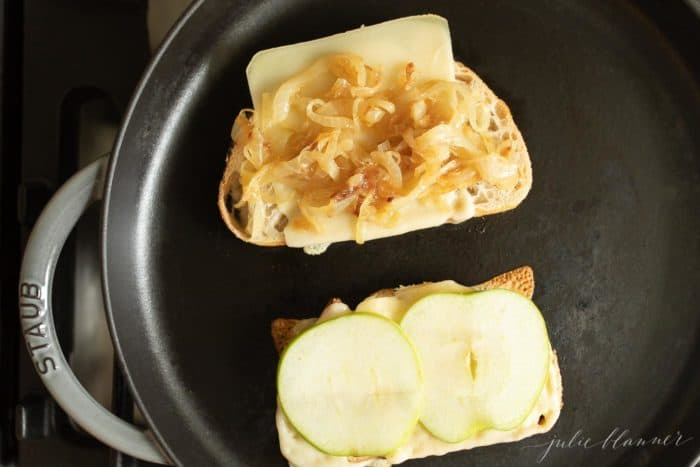 Cast iron skillet with 2 bread slices, cheese slices, apples and caramelized onions on top.