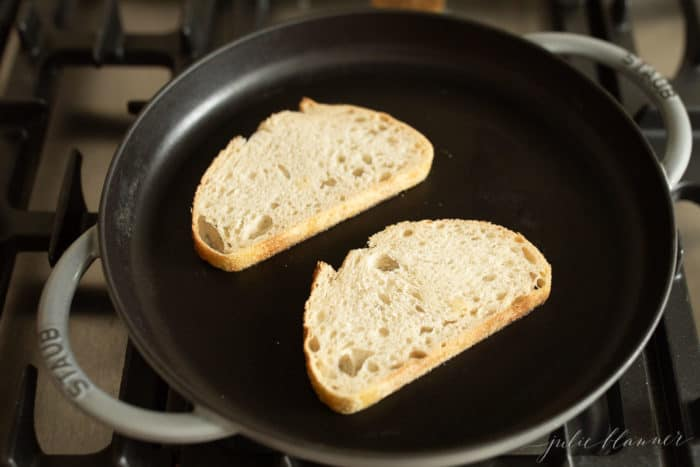 Cast iron skillet with 2 bread slices.