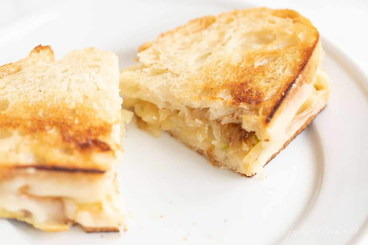 White plate with a sliced gourmet grilled cheese sandwich.