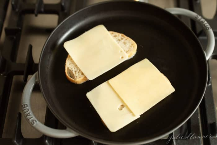 Cast iron skillet with 2 bread slices, cheese slices on top.
