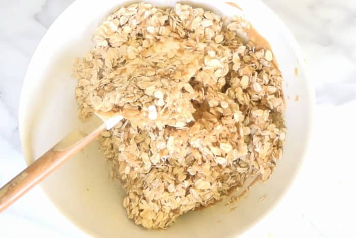 mixing granola rice peanut butter and honey with a spatula