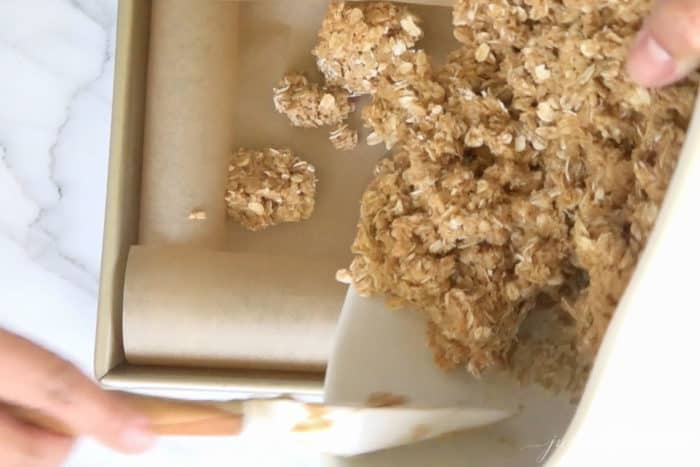 scooping no bake peanut butter bar mixture into baking dish