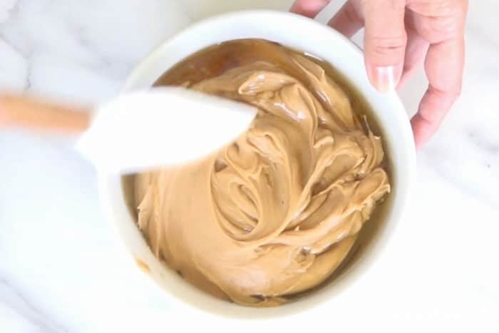 mixing peanut butter and honey together in a white mixing bowl