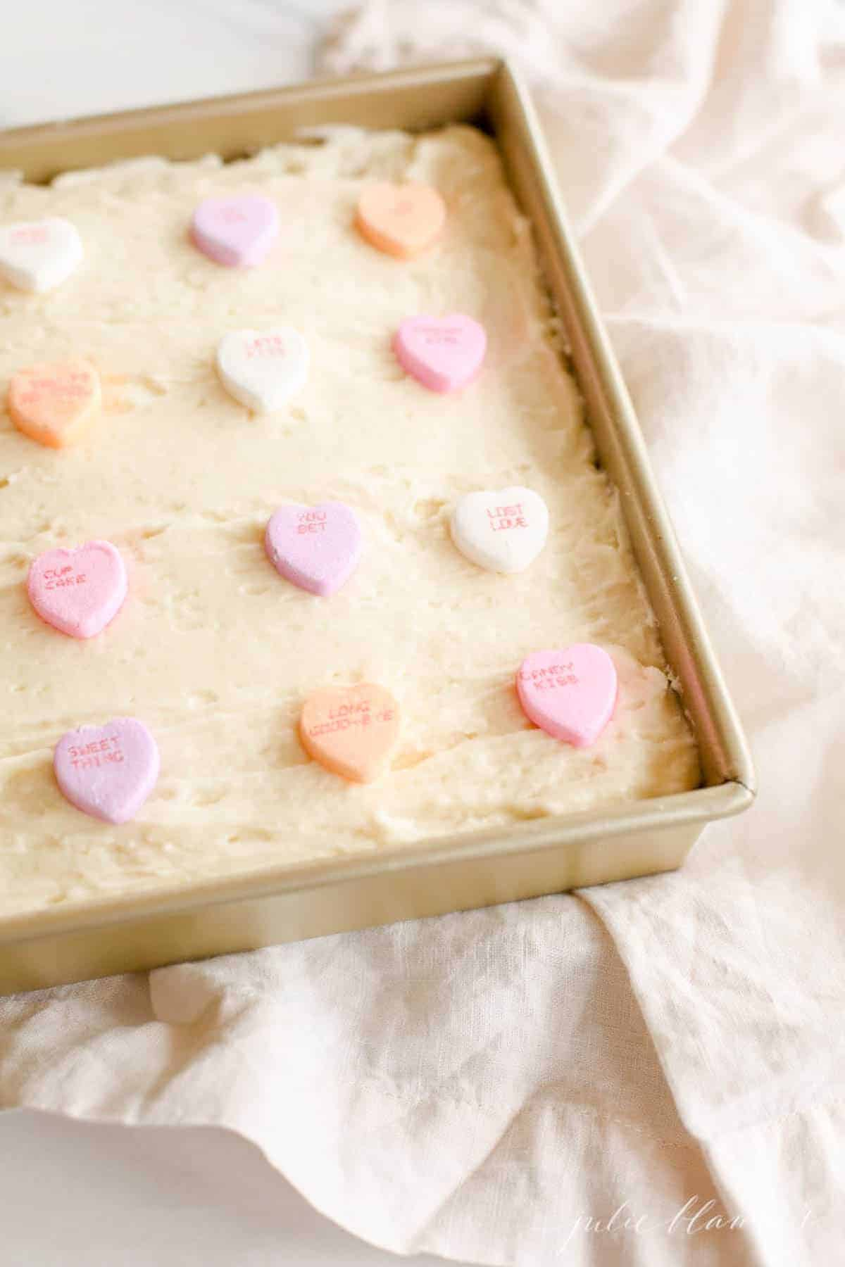 sugar cookie bars in gold baking pan topped with conversation hearts