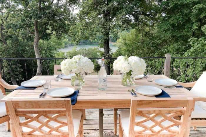 A wooden patio table set with hydrangea centerpieces, place settings, lake view in the background.