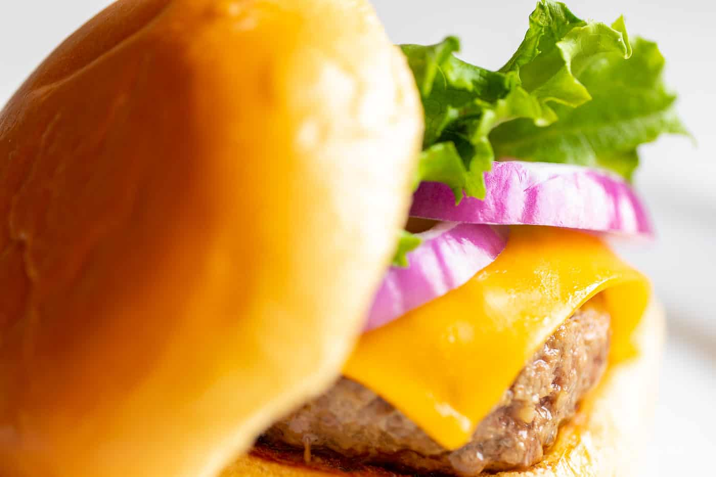 A juicy burger with lettuce, cheese, and onions on a white plate.