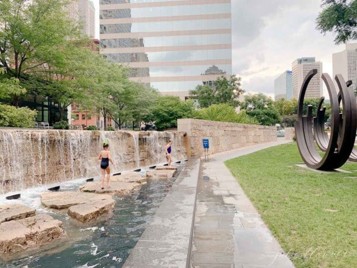 City scene with little girls skipping across rocks at a public fountain area.