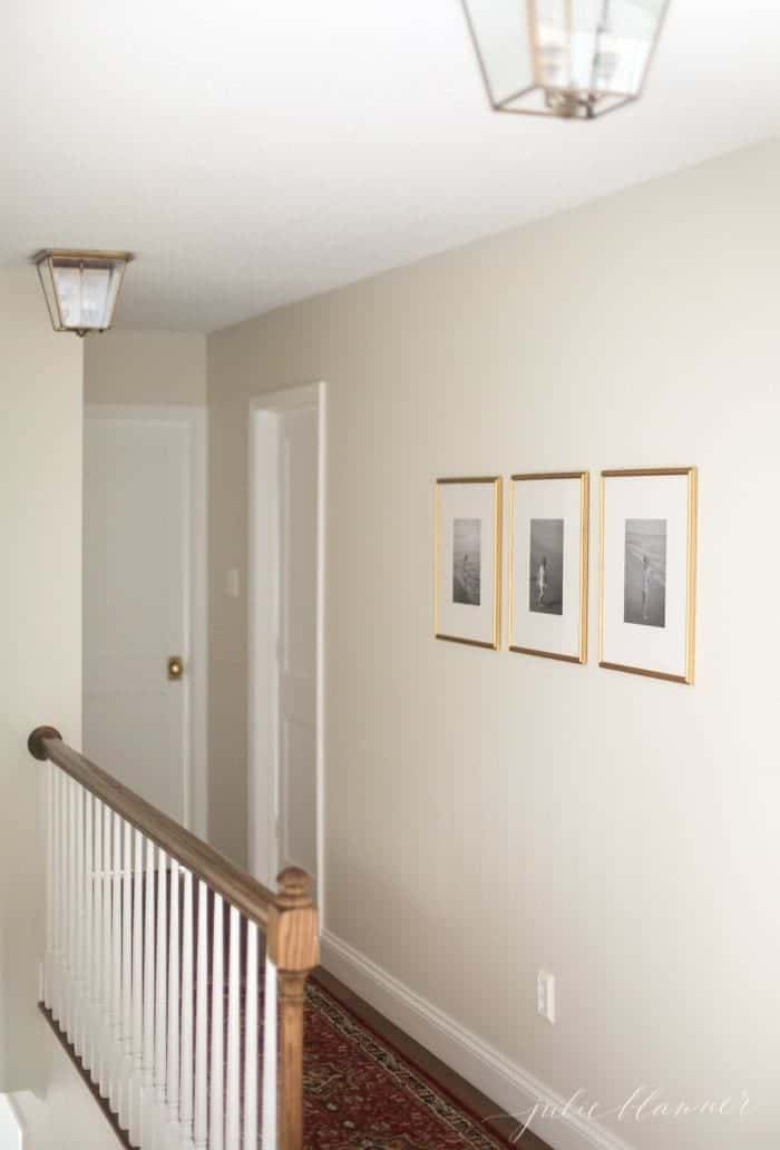 White hallway with 3 simple framed pictures in a minimalist house.