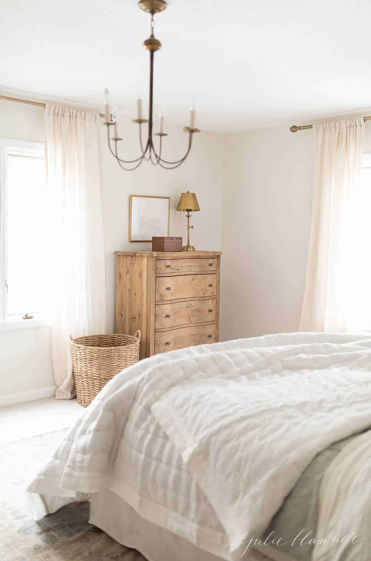 Simple white bedroom with a wooden dresser