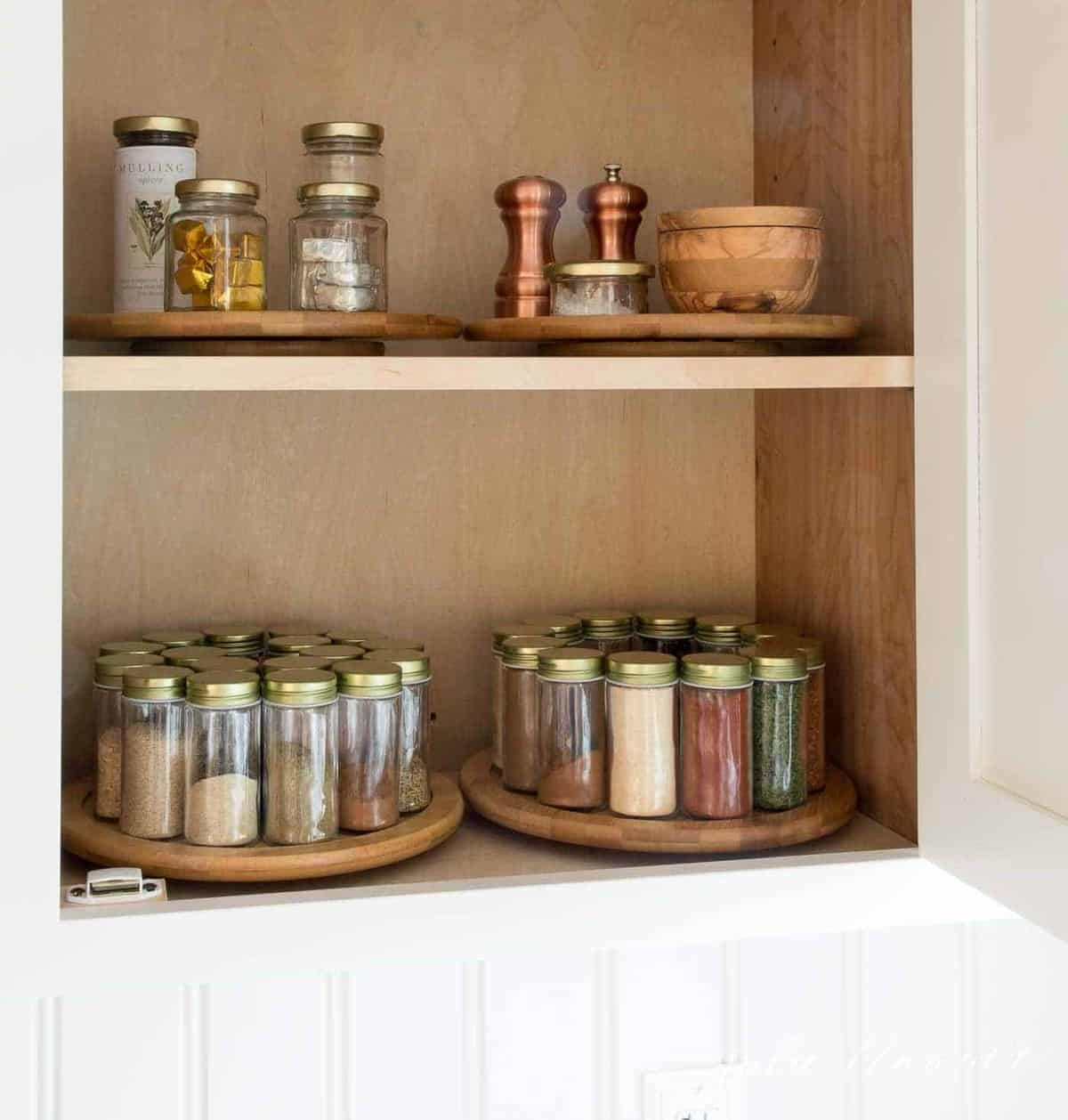Organized spice jars on lazy susans inside a cabinet.