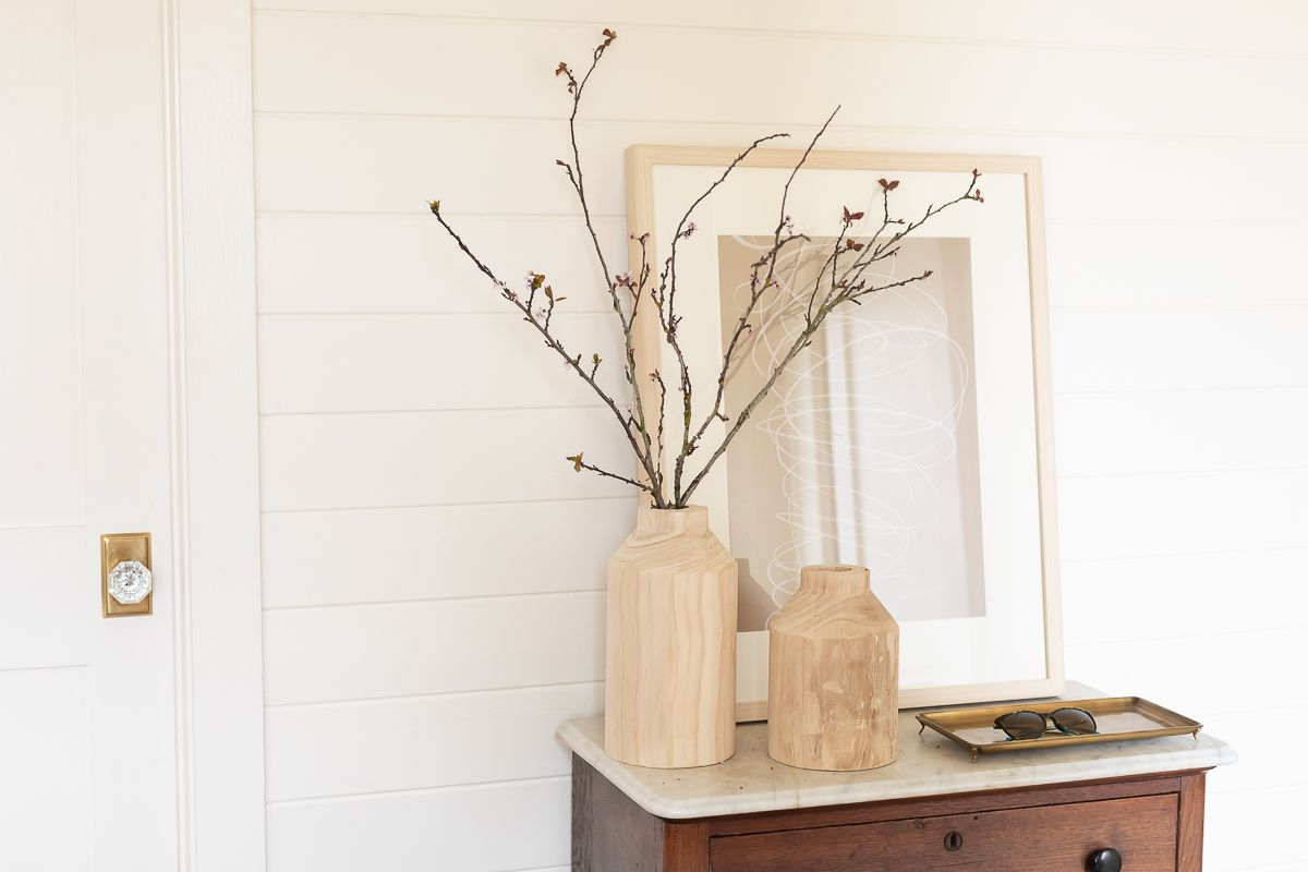 A white paneled mudroom with a wood dresser for storage.