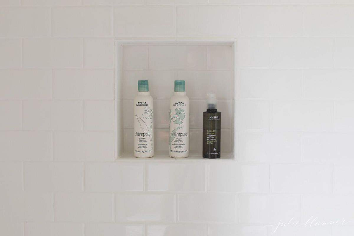 Clean white subway tile in a shower, shampoo bottles in a tile niche.
