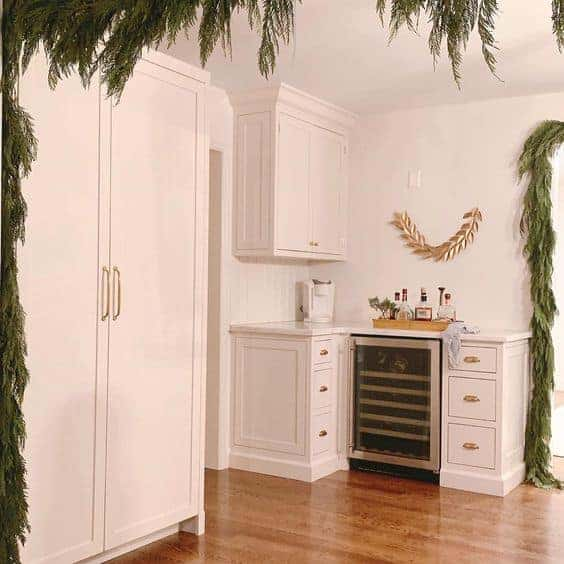 New kitchen decorated with Christmas greenery, white cabinets and wood floors.