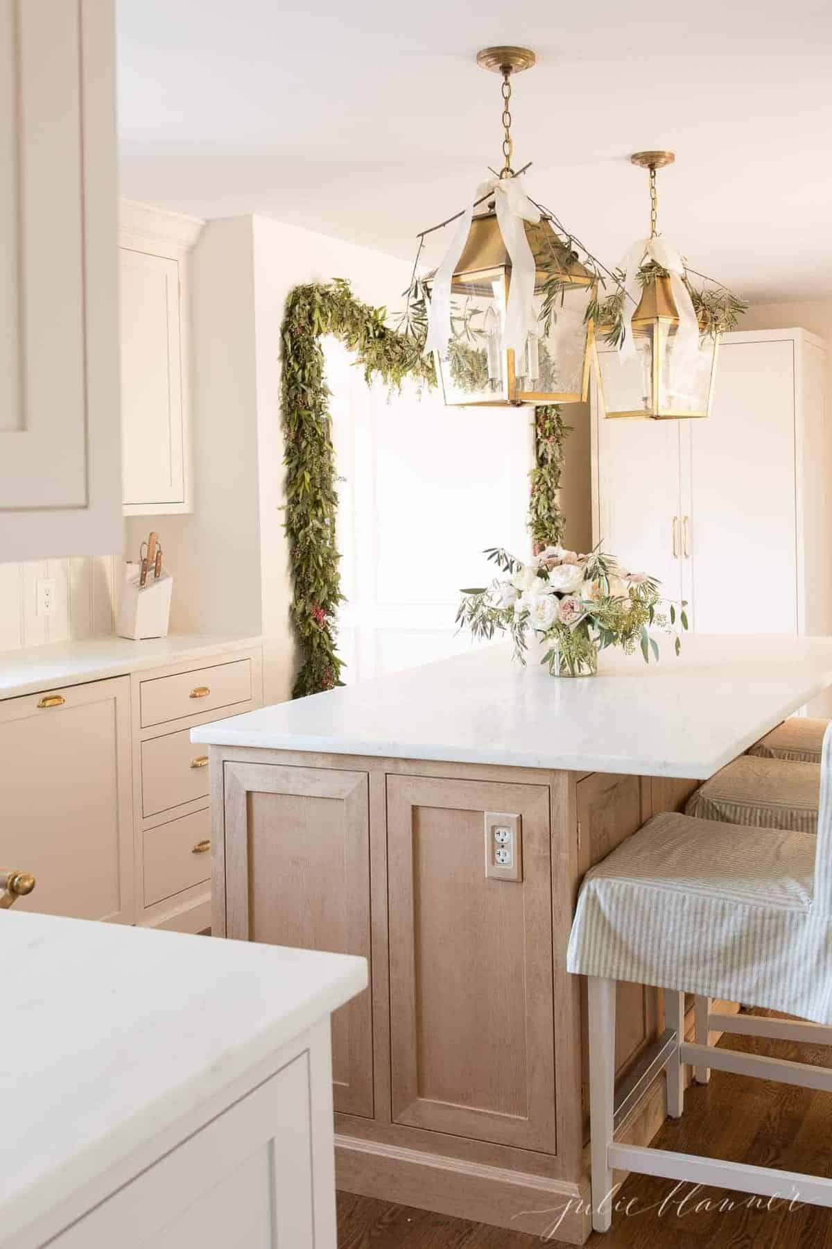 A Cream kitchen with a light wood island, brass lanterns, decorated for Christmas.