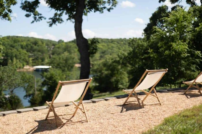Folding chairs on a quiet patio, simple living with a treed lake view.