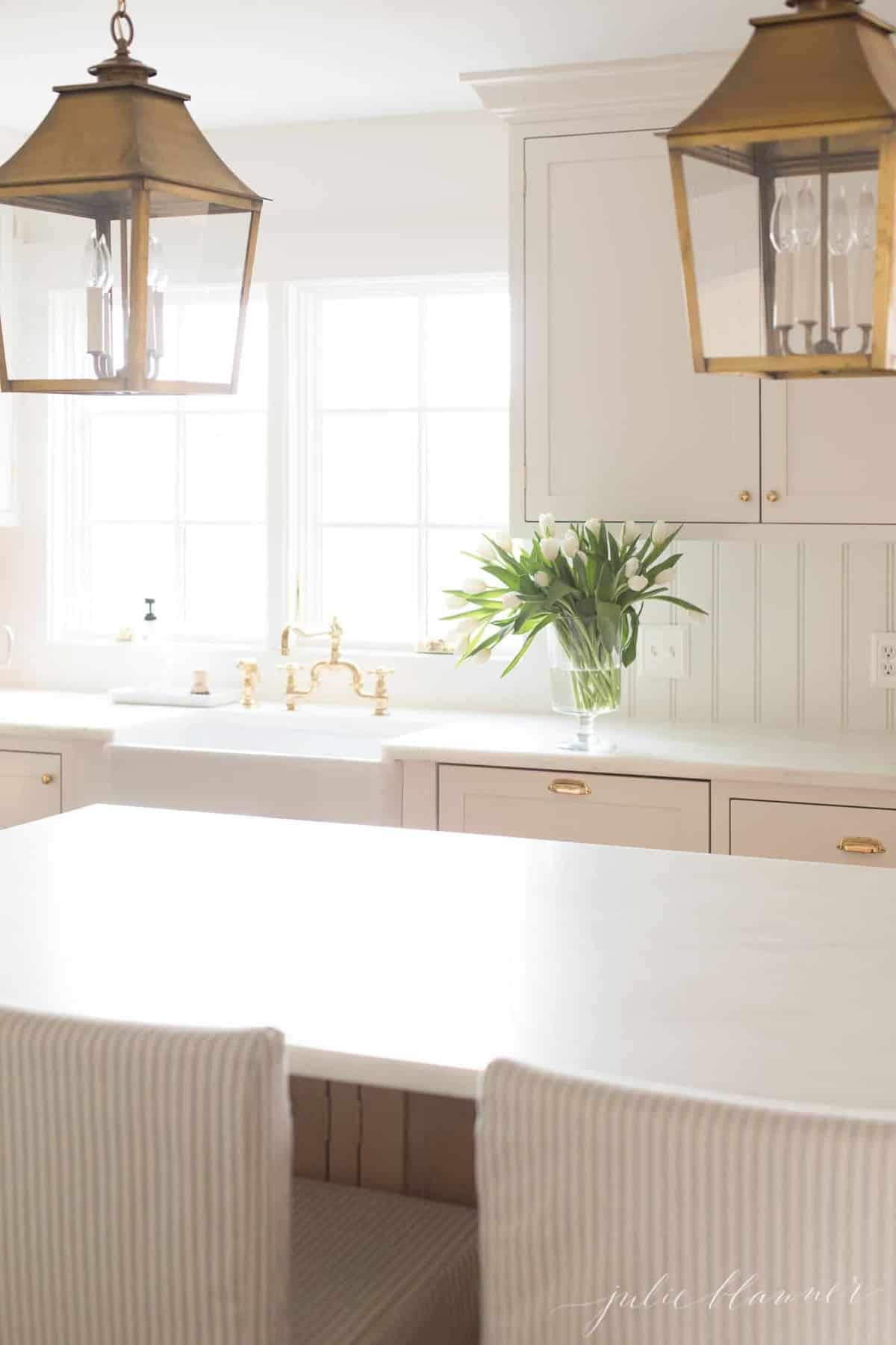 white minimalist kitchen with a single vase of tulips on the counter tops.