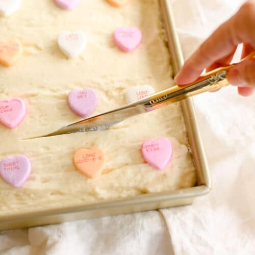 gold knife cutting sugar cookie bars with buttercream frosting