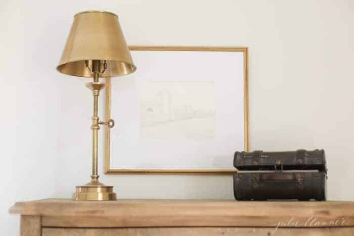 A wooden dresser with a piece of framed diy wall art, brass lamp.
