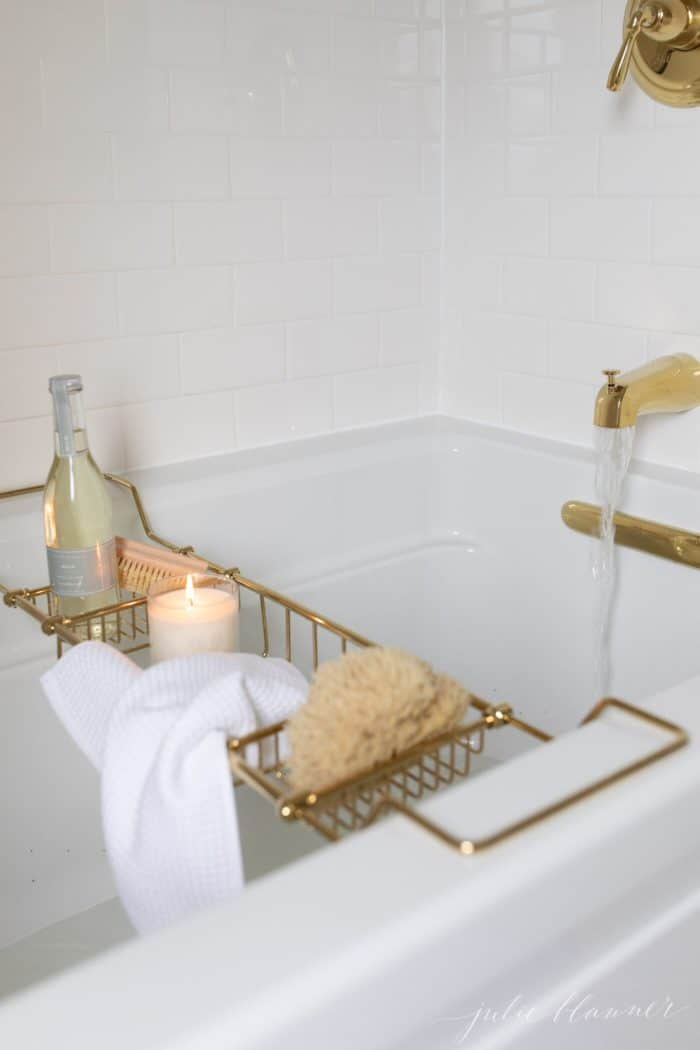 White bathtub with a brass tub tray filled with bath accessories, water running into tub.